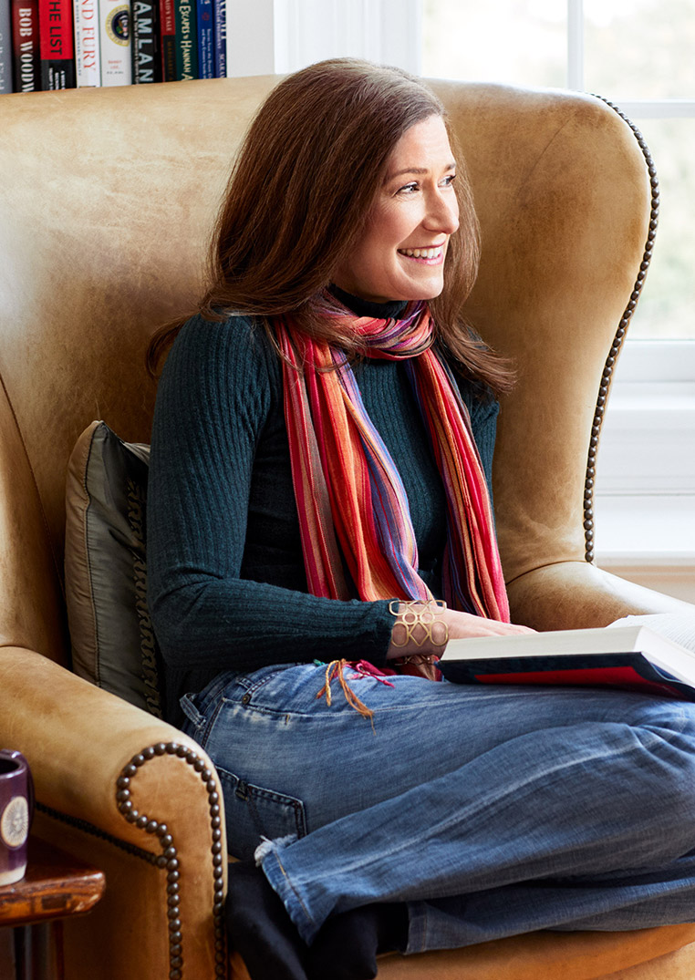 Amy Siskind sitting reading on chair